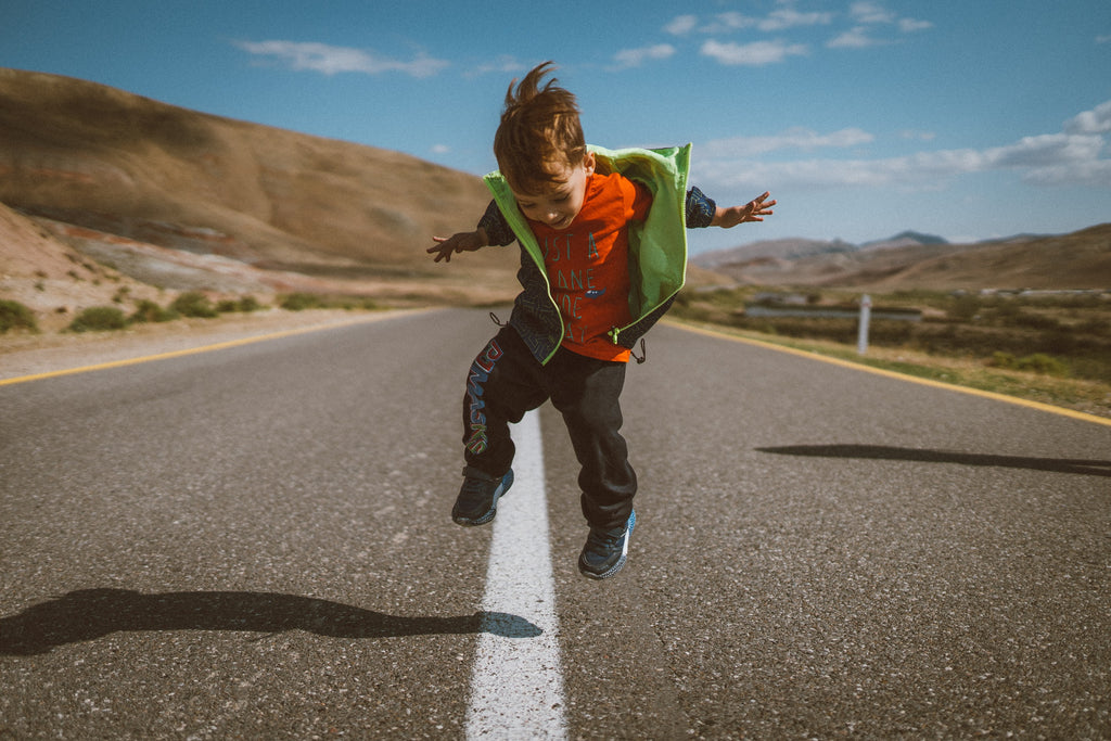 Little boy in the middle of an empty road, jumping, with views of hills behind him.