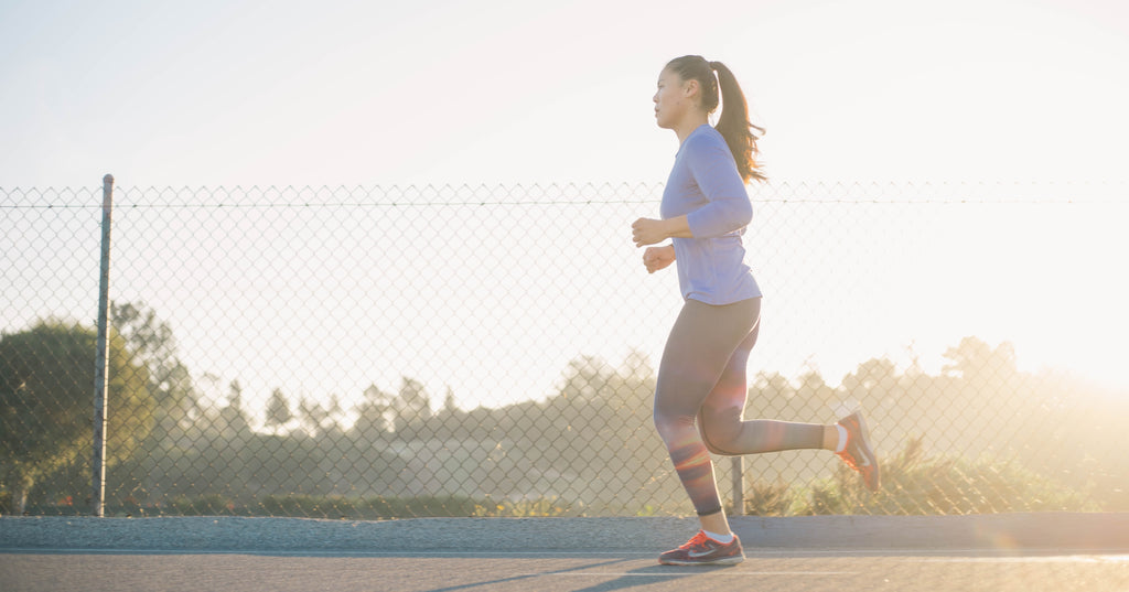 Woman wearing color blue long sleeves, black leggings and, a ponytail on her hair running during sunrise