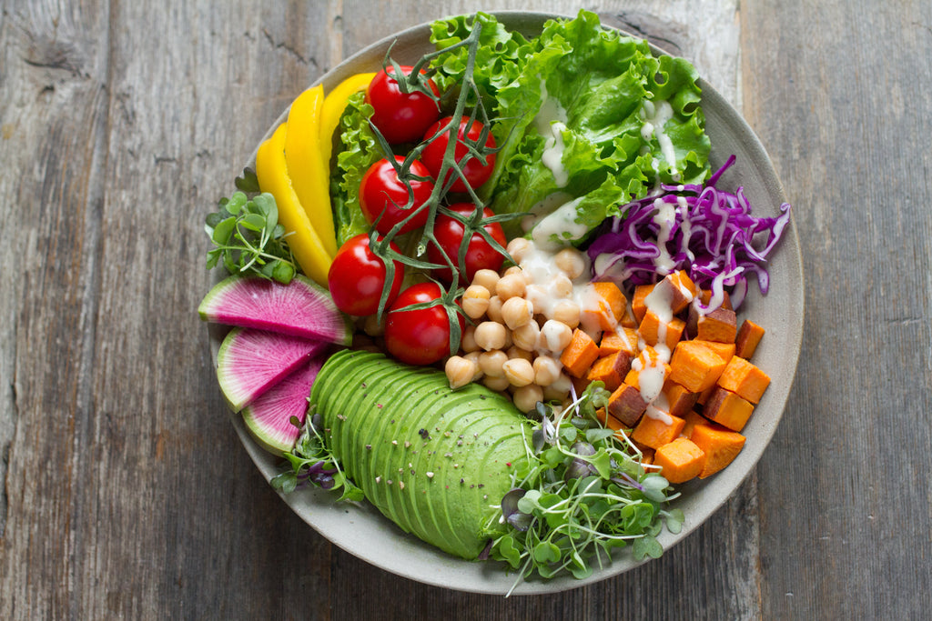 Bowl full of vegetables including vine tomatoes, avocado, radish, chickpeas, sweat potatoes and lettuce.