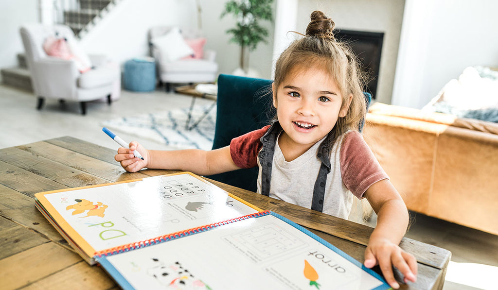 A little girl wearing a gray shirt smiling while studying alphabetical letters on the table  in the living room