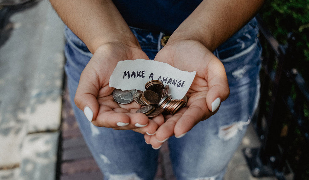 Women in blue shirt and tattered jeans, holding coins with two hands with a paper note: Make a change