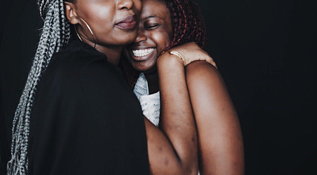 Two black women hugging. One is taller than the other, so we can't see her eyes, but she is wearing a black top with long silver braids and silver hoops. The woman she is hugging is smiling with her eyes closed, and smiling big.