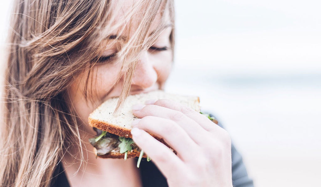 A girl with blonde hair eating a sandwich in a blurred background