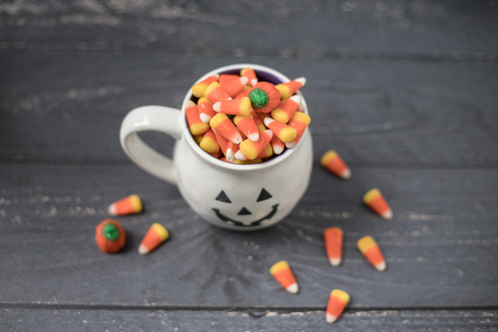 A white mug with a jack'o'lantern face sits on a wooden table. The mug is filled with candy corn, and a few pieces of candy corn lay around the mug.