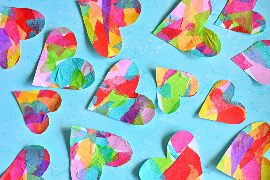 Rainbow cut out hearts laying on a sky blue background.