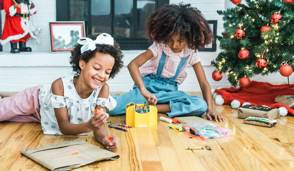 Kid in a white blouse holding a crayon while laying down on the floor and another kid on a pink blouse sitting while picking a crayon to write on their gifts beside a christmas tree