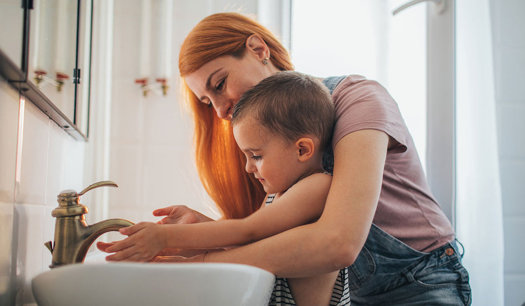 A mother in purple shirt carrying a child while washing hands in the sink