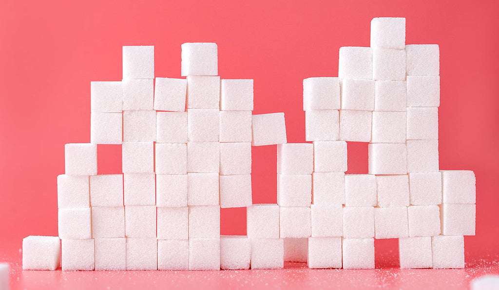 Sugar cubes piled vertically in a pink backdrop