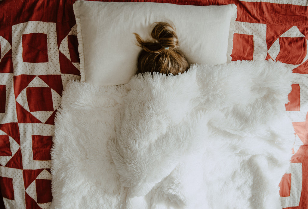 A woman with a ponytail covering herself with a soft white blanket while sleeping ina background of maroon designed bedsheet cover