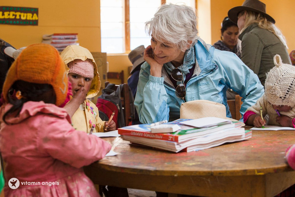 Women wearing a blue jacket is smiling and looking at the first child in a yellow jacket who is biting her nails while looking at another child in a pink jacket