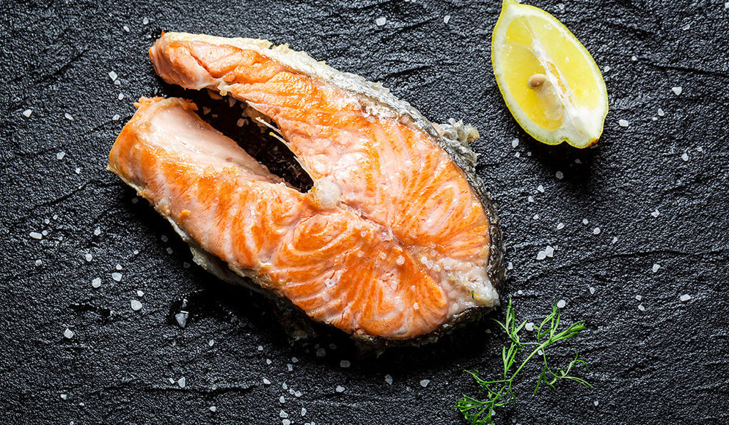 Cooked Salmon and sliced lemon on the right upper side and rosemary on the bottom with scattered salt on black background
