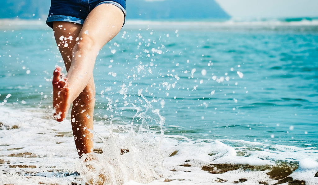 Woman in blue shorts kicking the water along the shore
