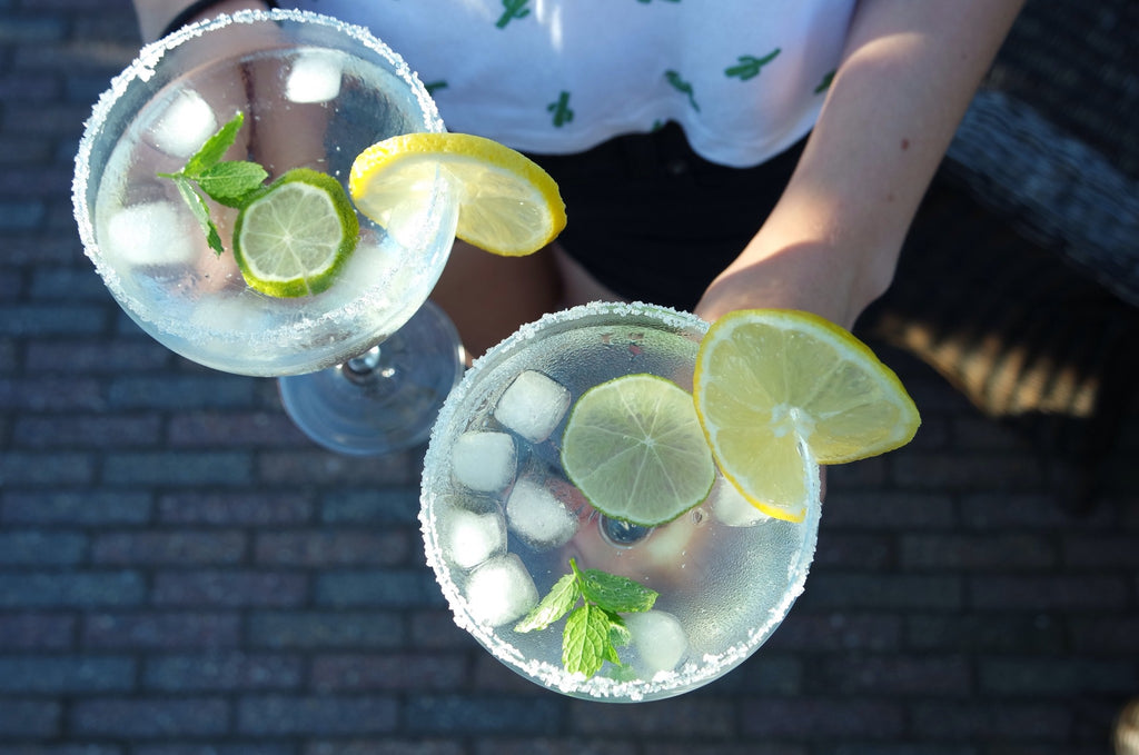 Top down view of two glasses being held. The glasses are wide, with a clear liquid, ice cubes, mint, limes and a lemon and salt on the edge.
