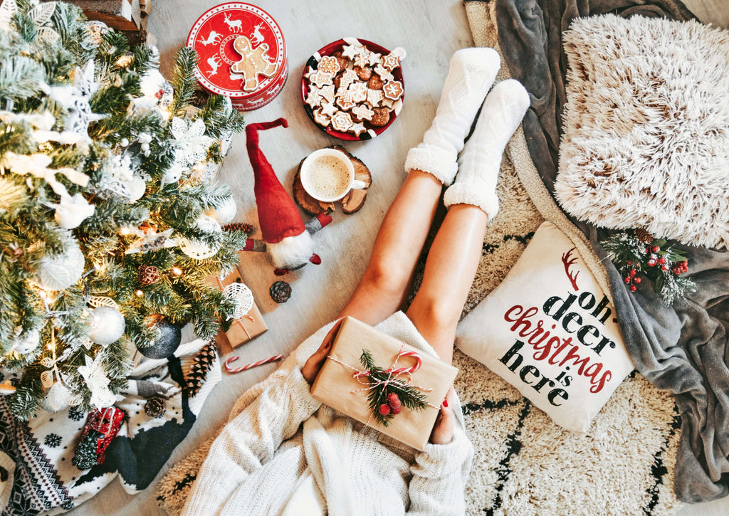 A woman who we can see from the torso down, is sitting on the floor in an oversize sweater and thick socks. Next to her is a decorated Christmas tree, pillows and blankets and a few bowls of snacks.