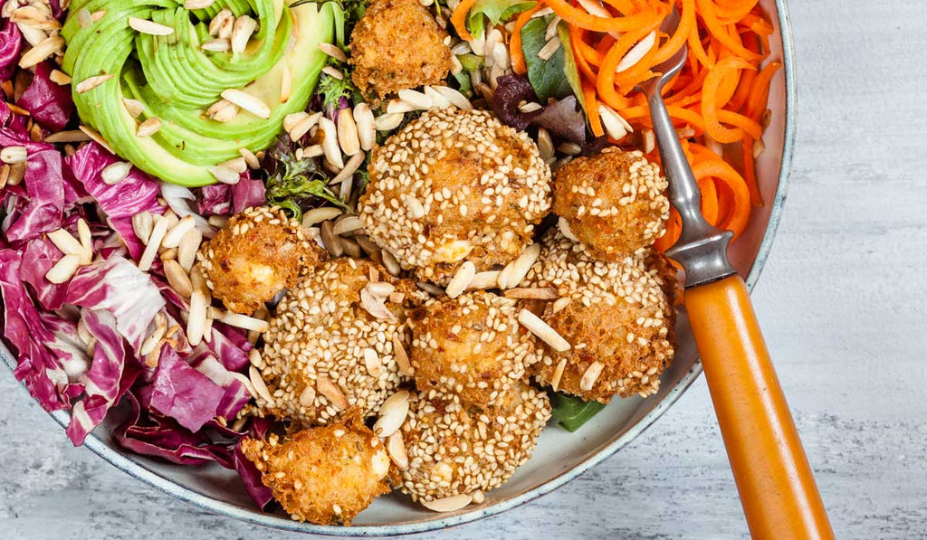 Plant Based Food in a bowl containing Avocado, Baked Falafel, Carrots, Red cabbage, Walnuts, Flaxseed with a fork on a side.