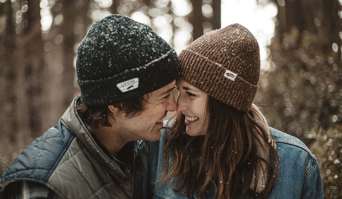 Couple flirting while having eye contact with their faces close during snow in the middle of the forest. Both of them wearing a beanie and blue jacket