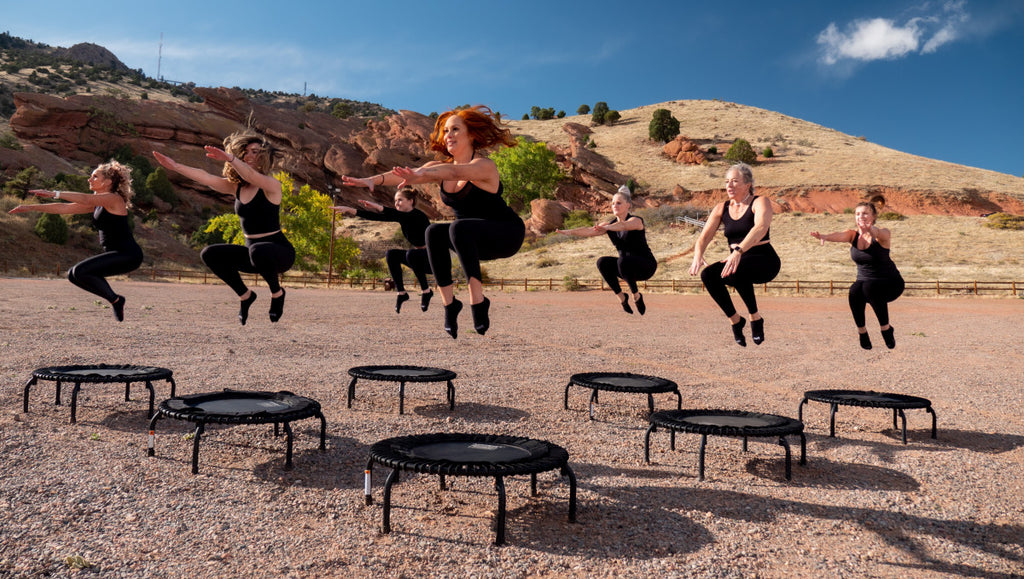 Women in black workout outfits, jumping on mini trampolines. They are all in the air with their knees bent. They are outside in a desert environment with some hills in the background.