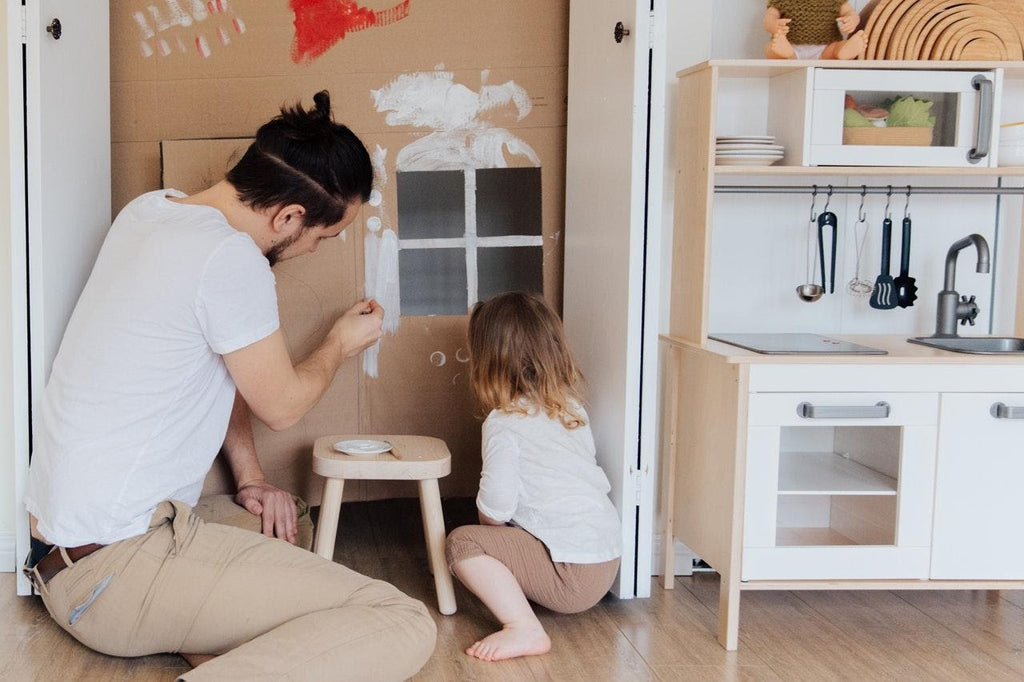 Father a young daughter are reusing their cardboard by painting a cardboard house with a small window. Next to them is a white kitchen playset.