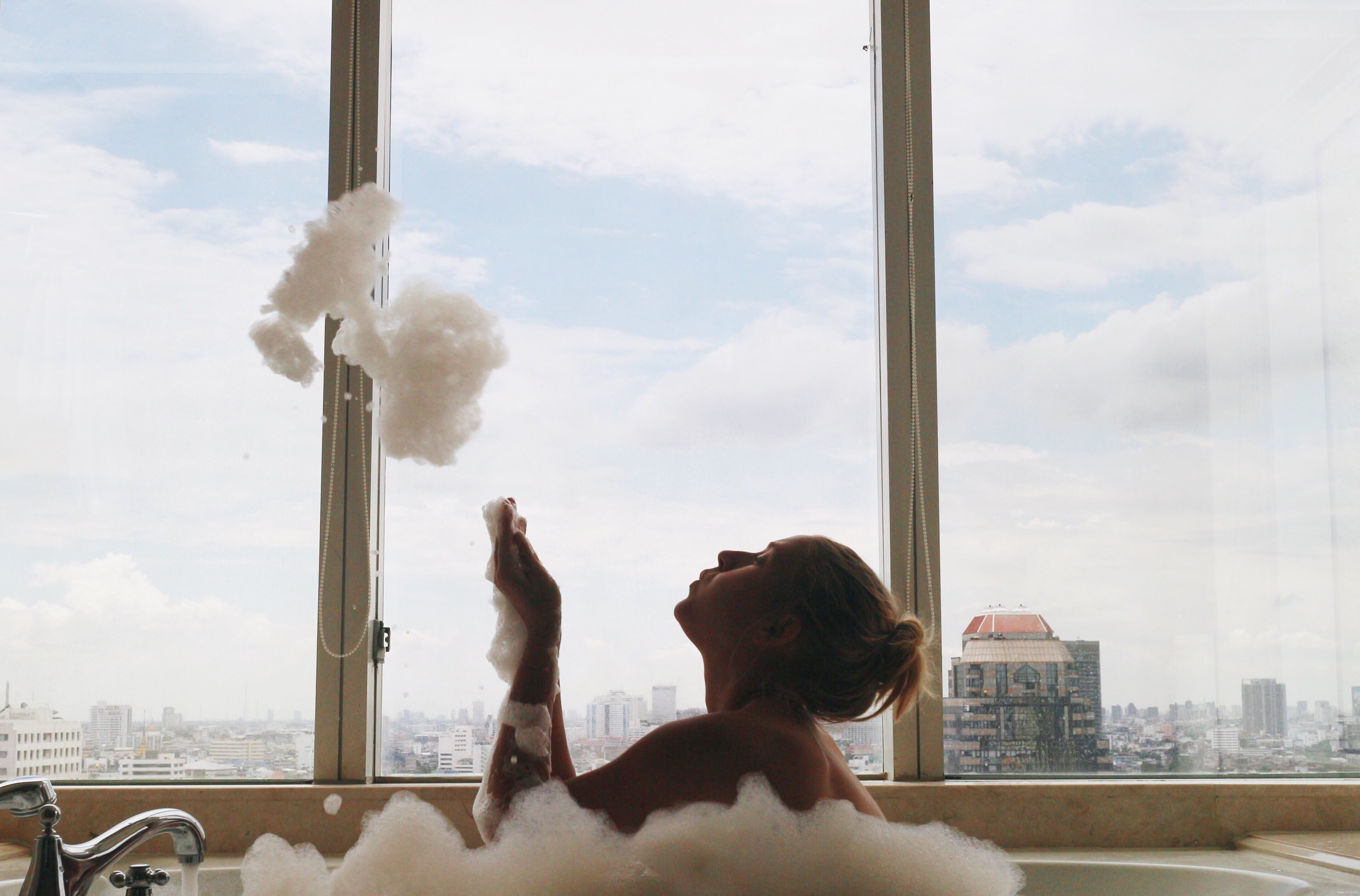 Woman sits in a bathtub, playing with the foam from a bubblebath. Behind her are 3 large window panels with a city view.