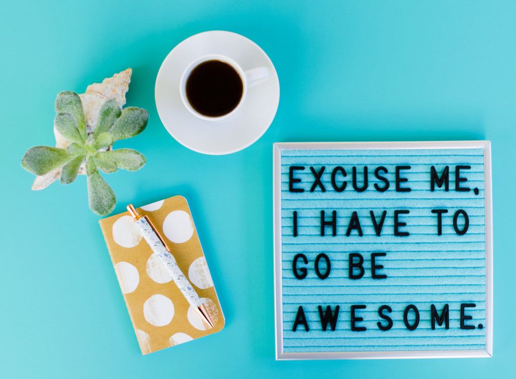 A bright blue backdrop with a cup of coffee, a small succulent, a yellow notebook with large white polka dots and a white pen on top of it, next to the notebook is a letter board that says: Excuse me, I have to go be awesome.