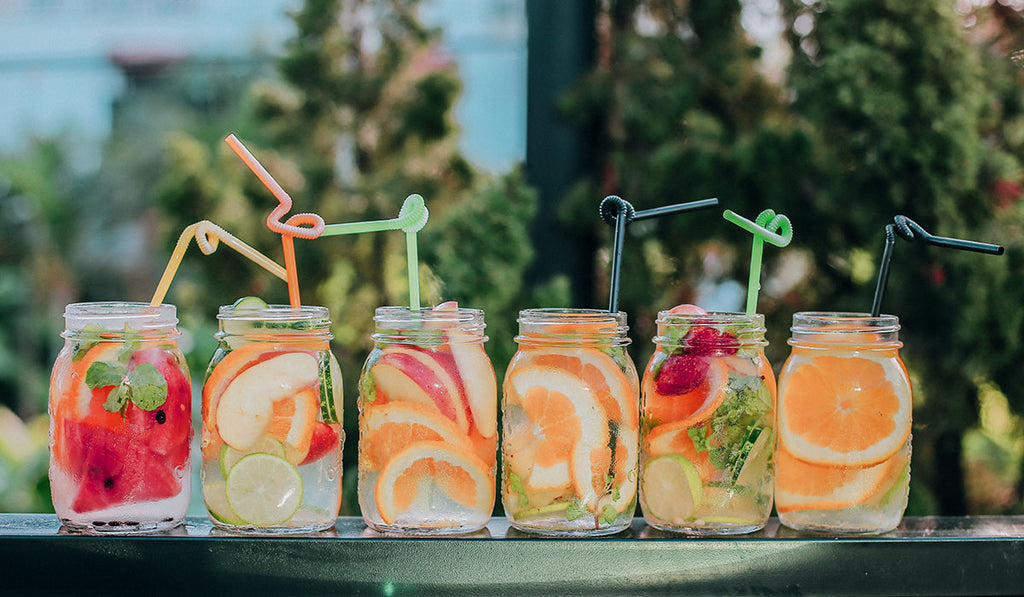 Different drinks in a mason jar with watermelon, apple, orange, cucumber place in the deck railings during daylight
