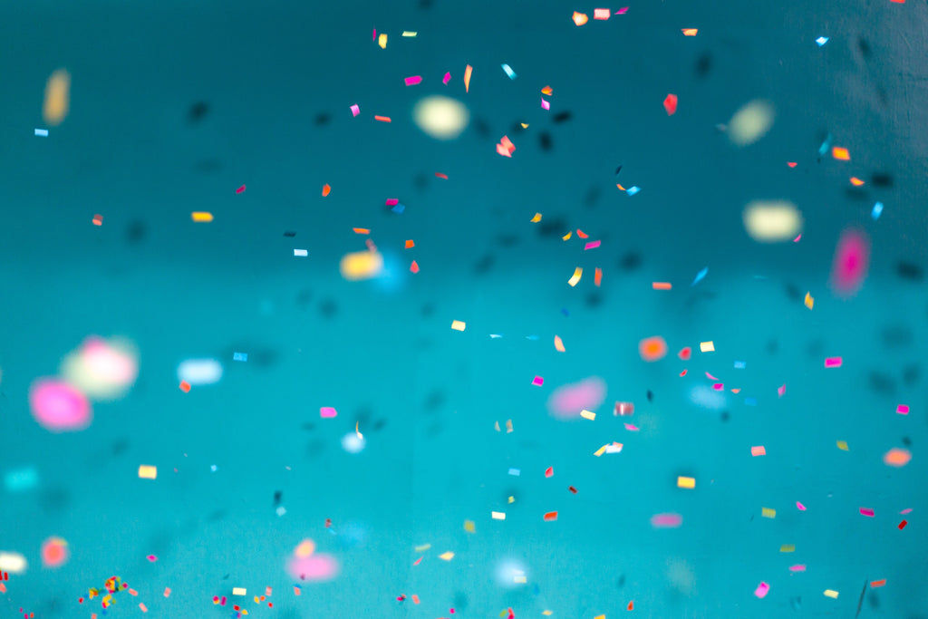 Scattered confetti with different colors in a cyan backdrop