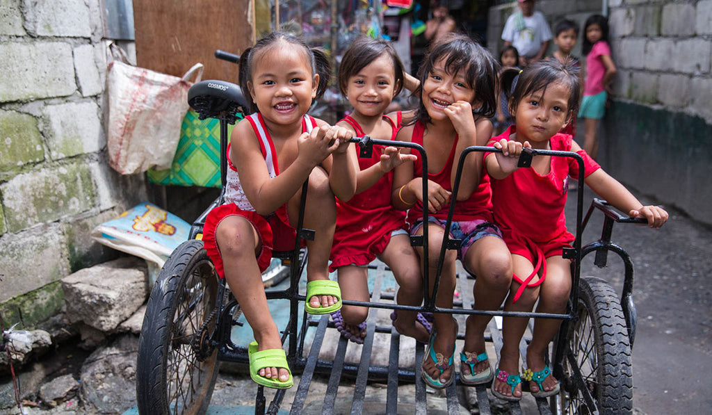 Four kids wearing red clothes smiling while riding in a bicycle sidecar while at the back are people looking at them from afar