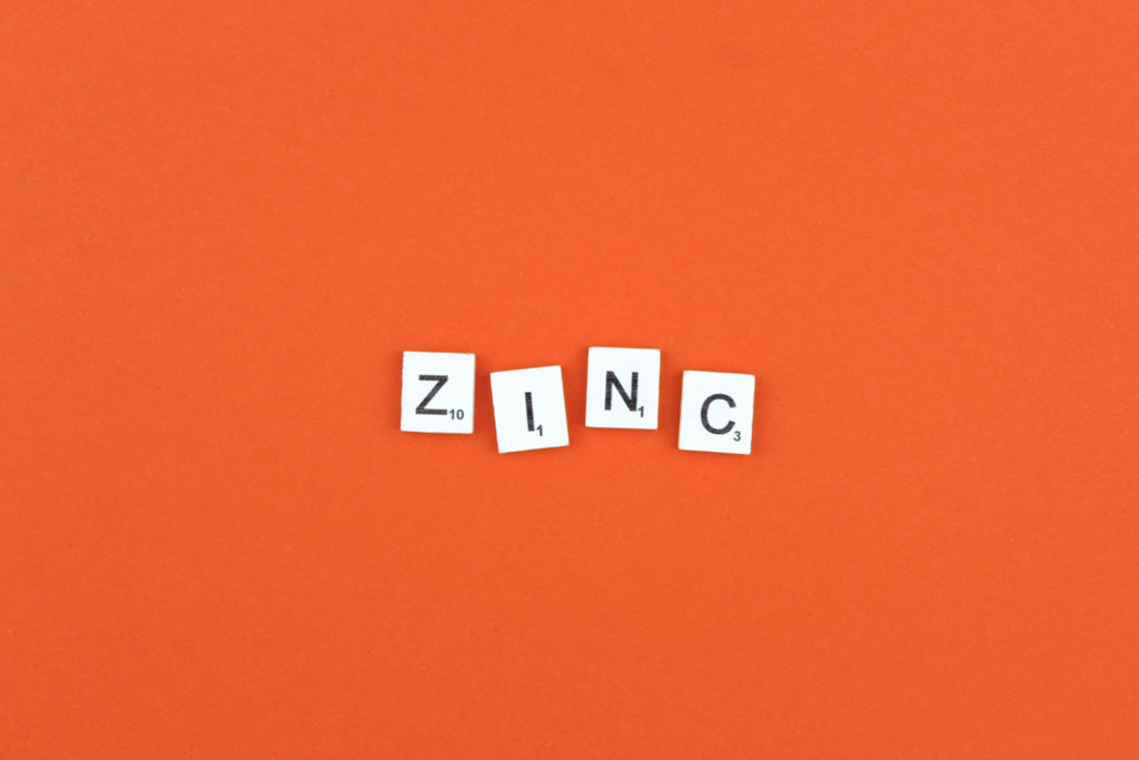 Scrabble tiles on an orange background that spell the word ZINC.