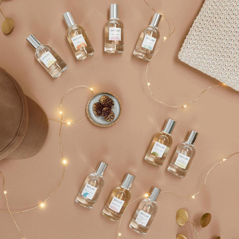 Perfume bottles arranged on tan background with fairy lights