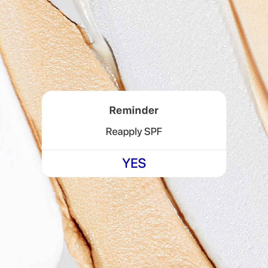 Phone alert reminder that says Reapply SPF, with a button that says YES. Textured cream in the background.