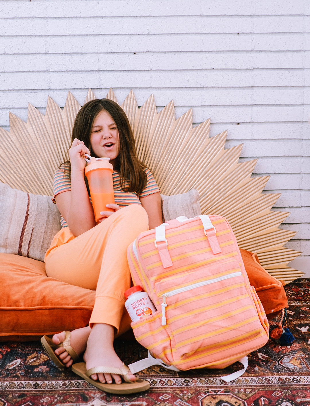 Girl sitting on an orange poof making a silly face, holding a shaker with an orange drink, and her backpack for school in front of her.