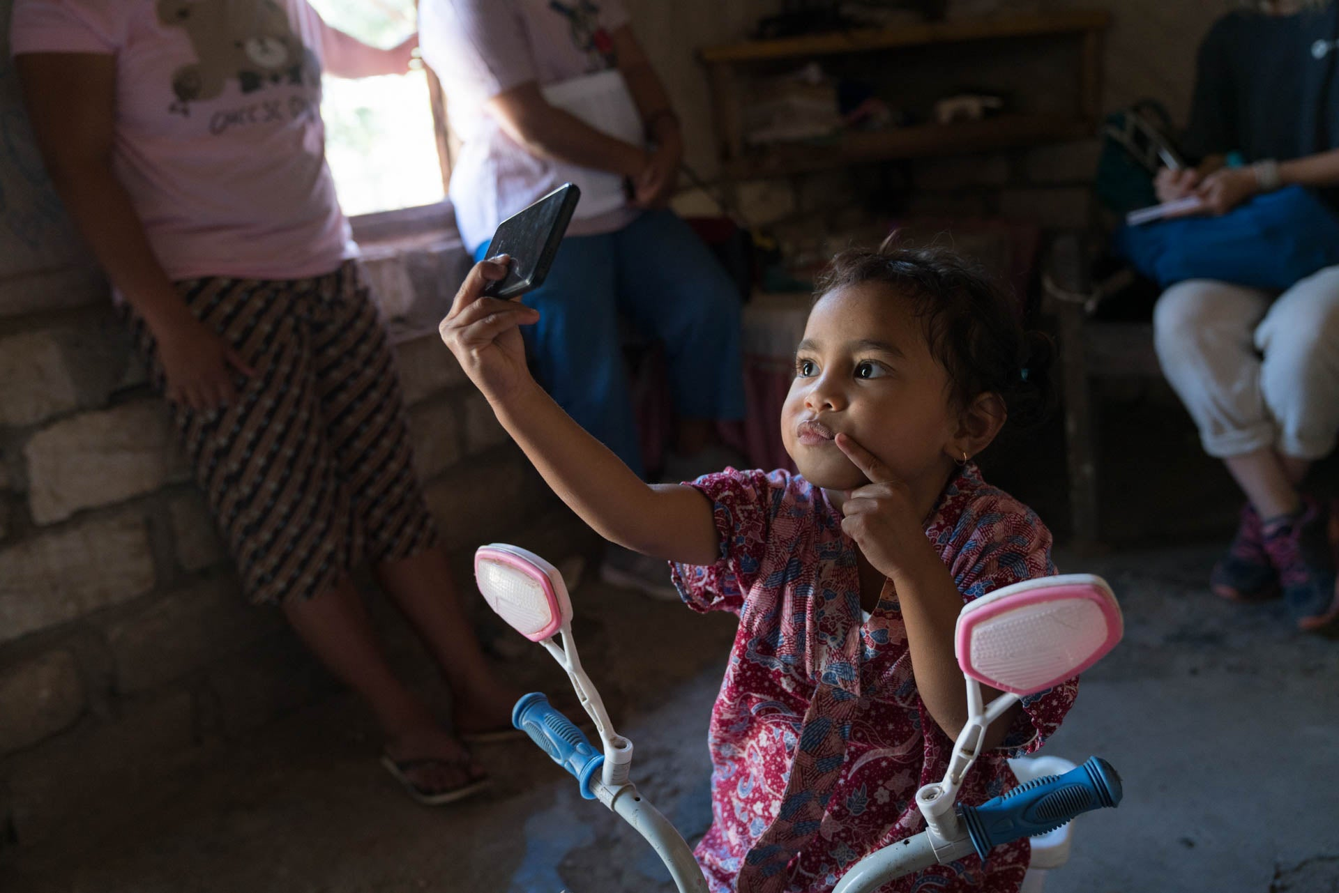 A little girl sitting on a bike, taking a selfie inside of a small brick home.