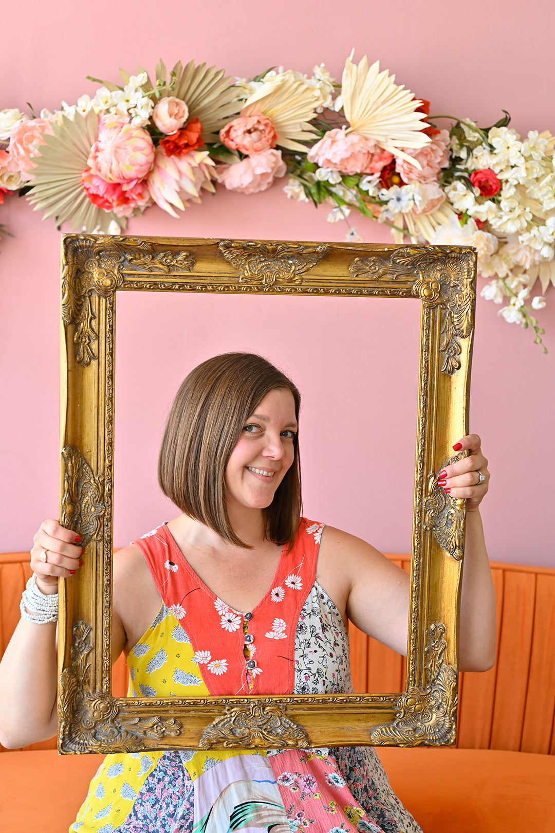Kelly sits in a colorful dress holding a gold picture frame around her face. There is floral decor above her.