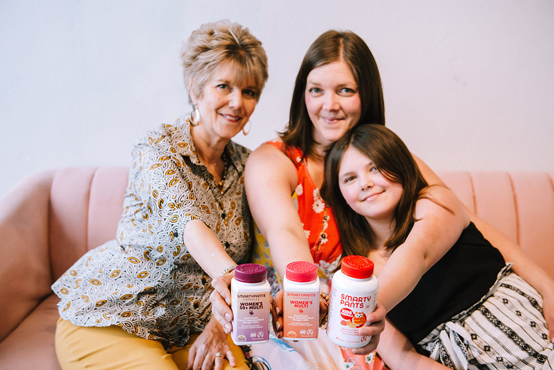 Three women sit on a couch, a grandmother, mother and young daughter. They all hold SmartyPants Vitamins products, capsules for mom and grandmother, and Kids Formula for the daughter.