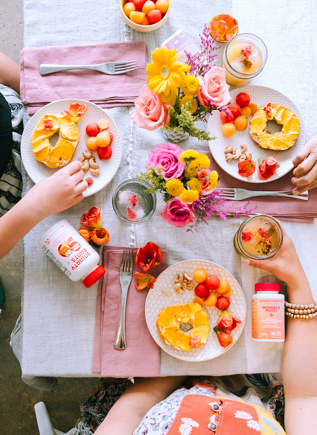 A table set, shot from above. On the table are flower bouquets, breakfast plates with bagels and fruit, and SmartyPants Vitamins vitamins. We see the hands of the grandmother, mother and daughter.