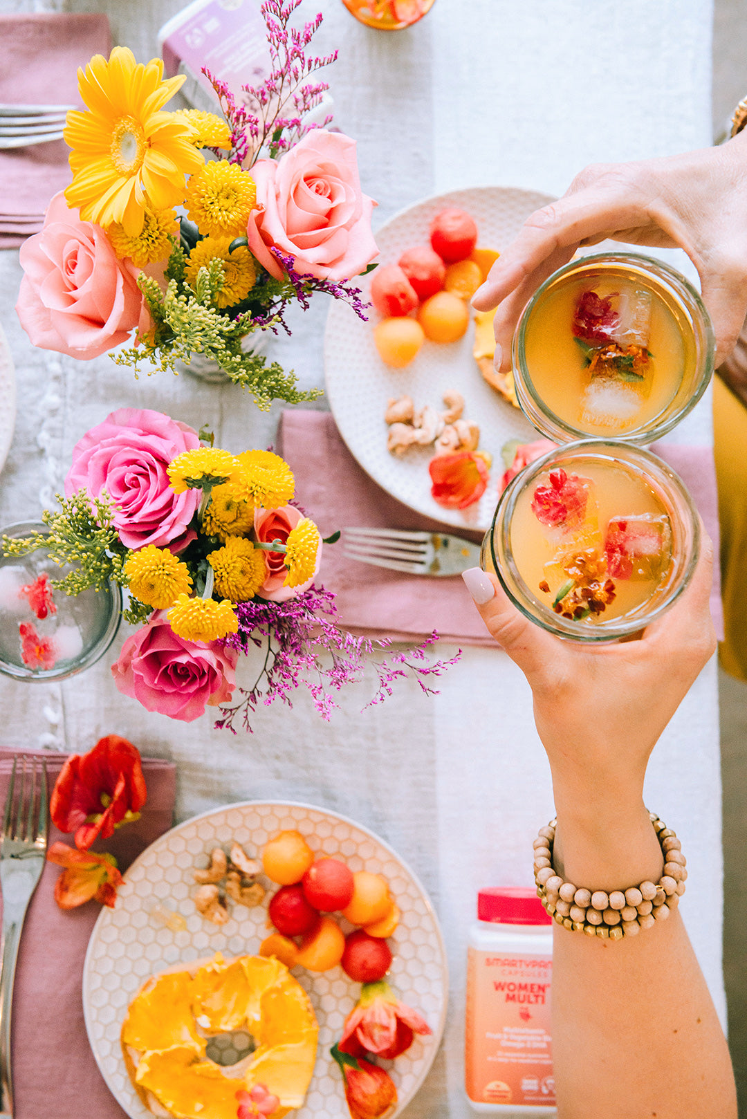 Table set, shot from above. The table is set with flowers and breakfast plates with bagels and fruit. We see two women's had cheers-ing with mimosas in mason jars, with flower petals in the mimosas.