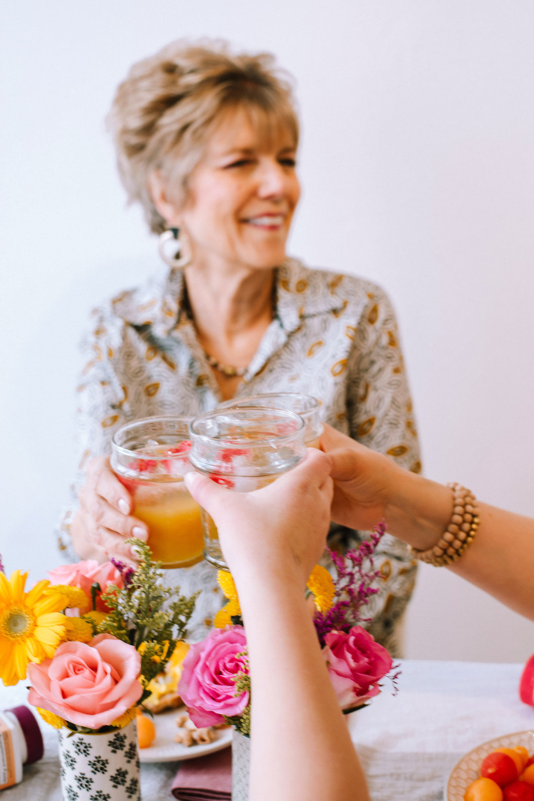 View of grandmother in printed blouse, sitting behind a vase of flowers, and cheers-ing her drink with mother and daughter's hands.