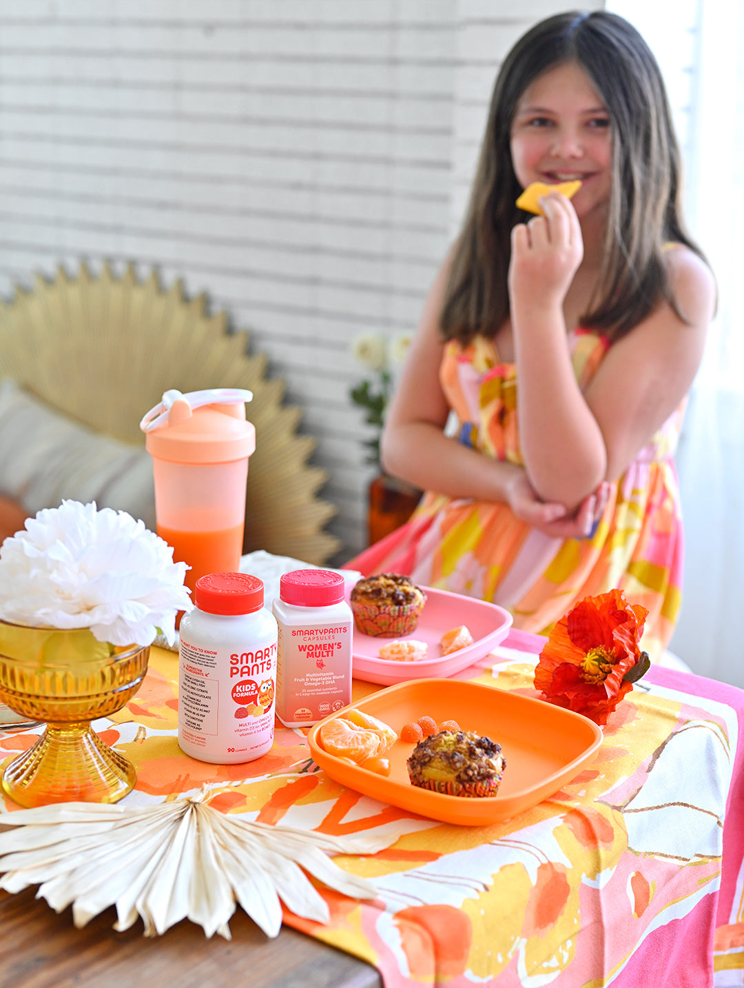 Girl sits at the breakfast table eating fruit and muffins. SmartyPants Women's Multi Capsule and SmartyPants Kids Formula are on the table.