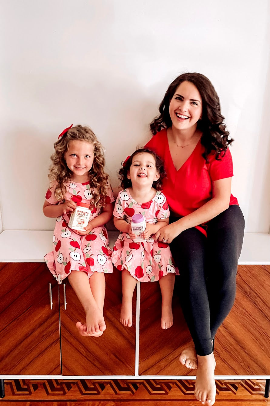 Woman sits on bench at home with her two little girls in matching apple print dresses. The girls are holding SmartyPants vitamins.