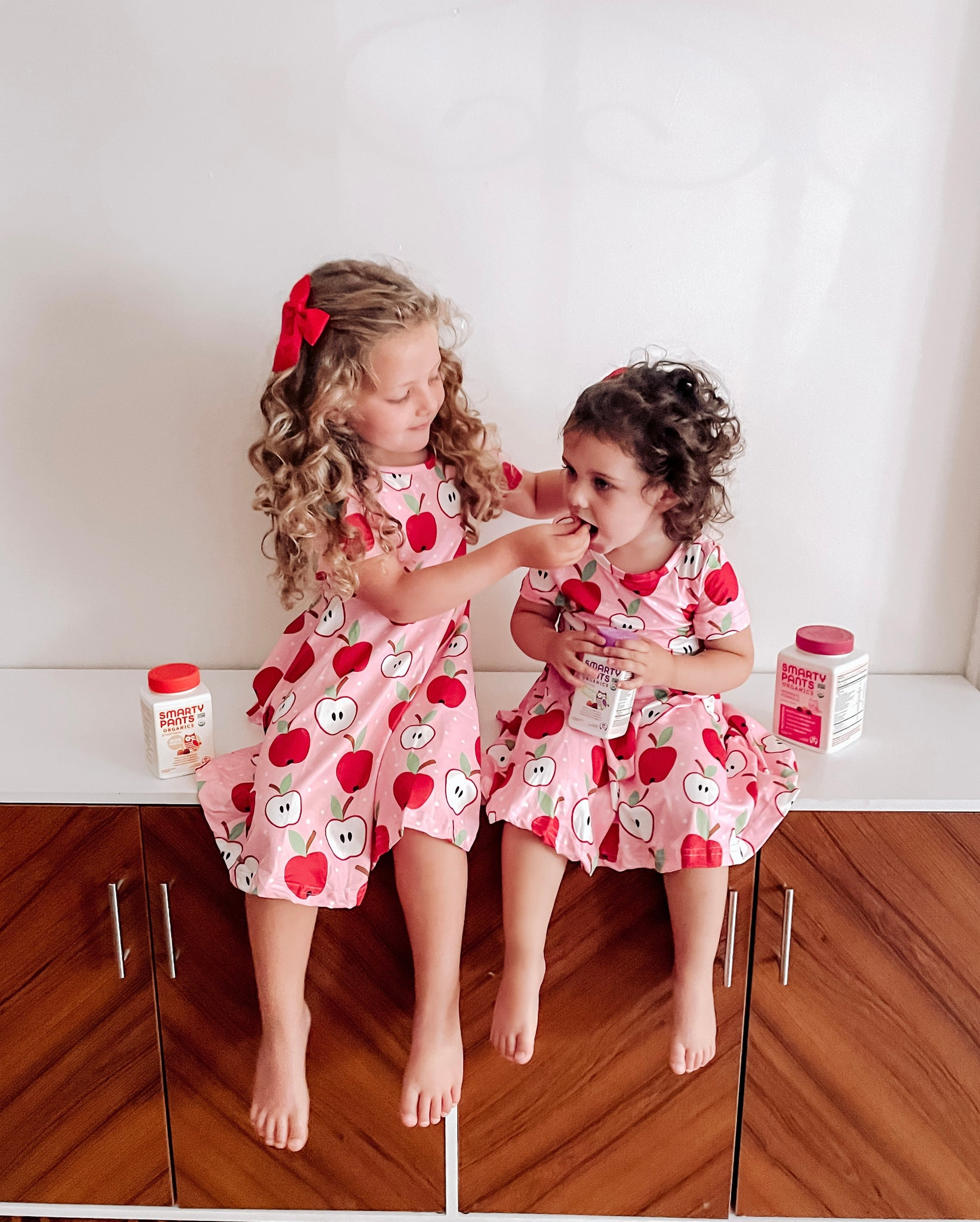 Two little girls sit inside on a bench, in matching apple print dresses. One little girl is feeding the other a SmartyPants Vitamins gummy.