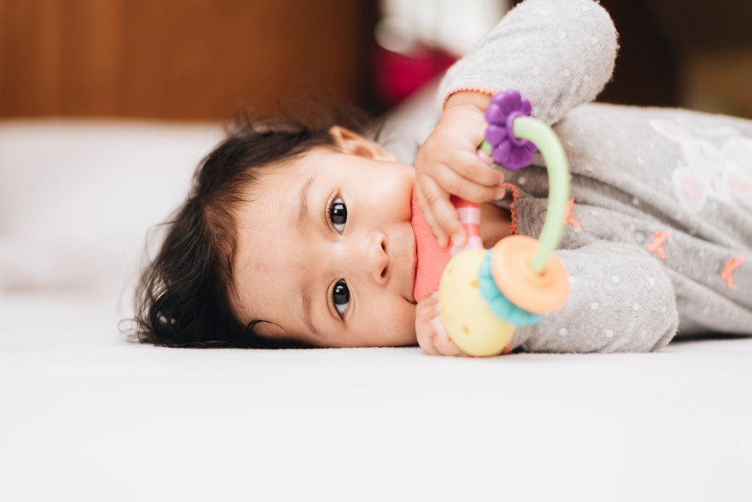 Baby laying down, with a teething toy in their mouth