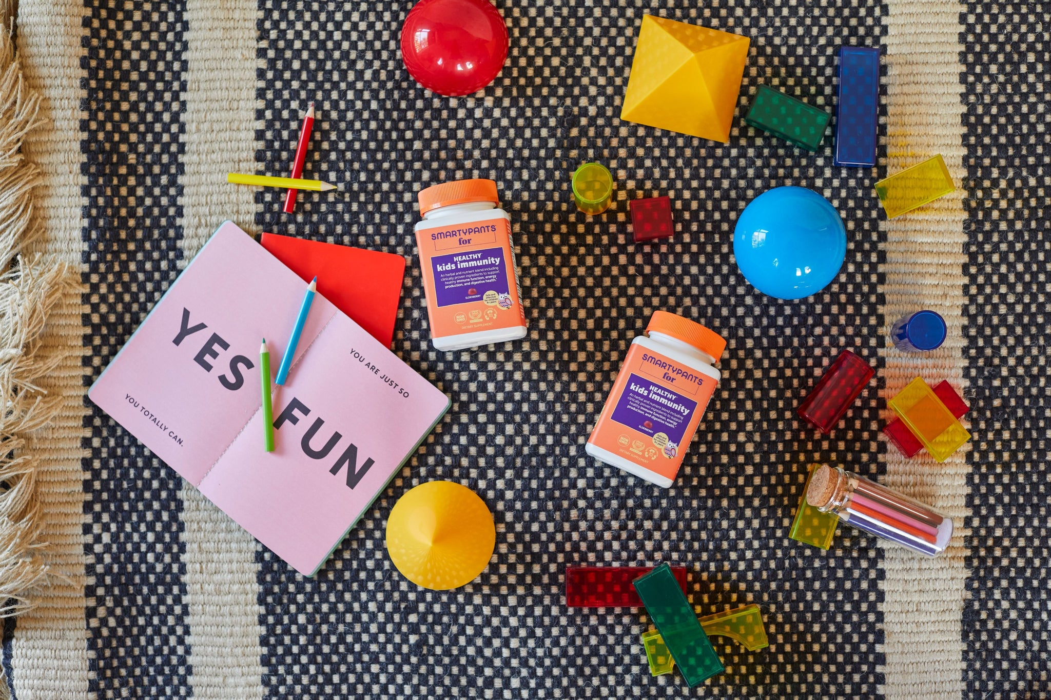 Two SmartyPants Healthy<sup>‡</sup> Kids Immunity* laying on a grey and white striped rug. Next to the bottles are kids toys like balls and blocks, colored pencils, and a book open to two pages. One page says YES and the other says FUN.