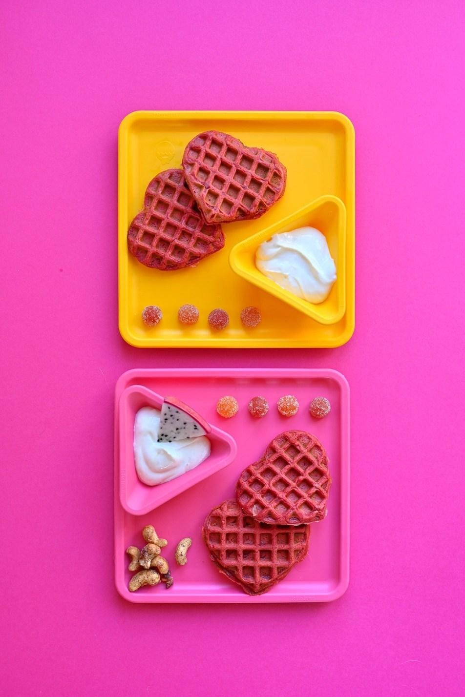 Pink and yellow kids plate on a pink background. The plates have SmartyPants Kids gummies, yogurt, dragonfruit and beet hear-shaped waffles.