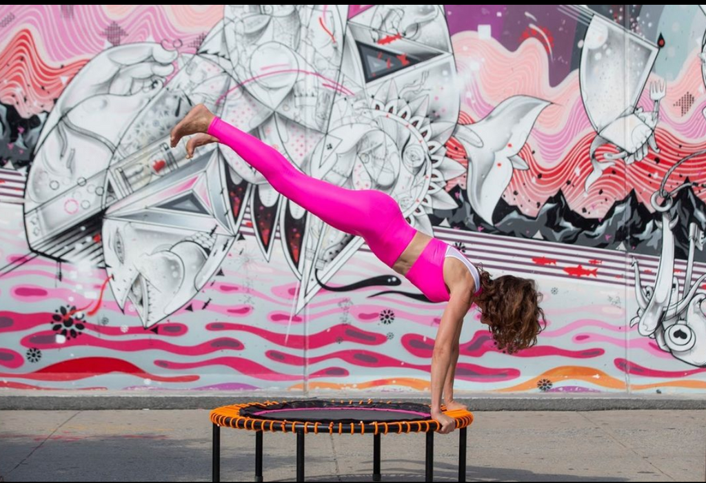 Woman in hot pink workout top and pants, working out on a trampoline. Her arms are straight on the edge of the mini trampoline and legs are up in the air. She is outside in front of a pink, black and white mural.