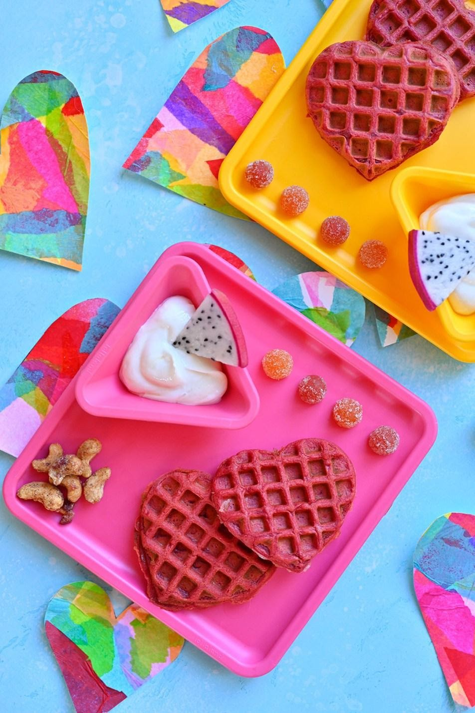 Two kids plates, yellow and pink on blue table surrounded by cut out hearts. The plates have pink heart shaped waffles, kids gummies, yogurt and nuts.