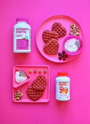 Pink background with two kids plates, both pink. Next to the top plate is SmartyPants Women's Formula and next to the bottom plate is SmartyPants Kids Formula. On the plates are pink heart-shaped waffles, SmartyPants gummy vitamins, yogurt with dragonfruit slice, and cashews.