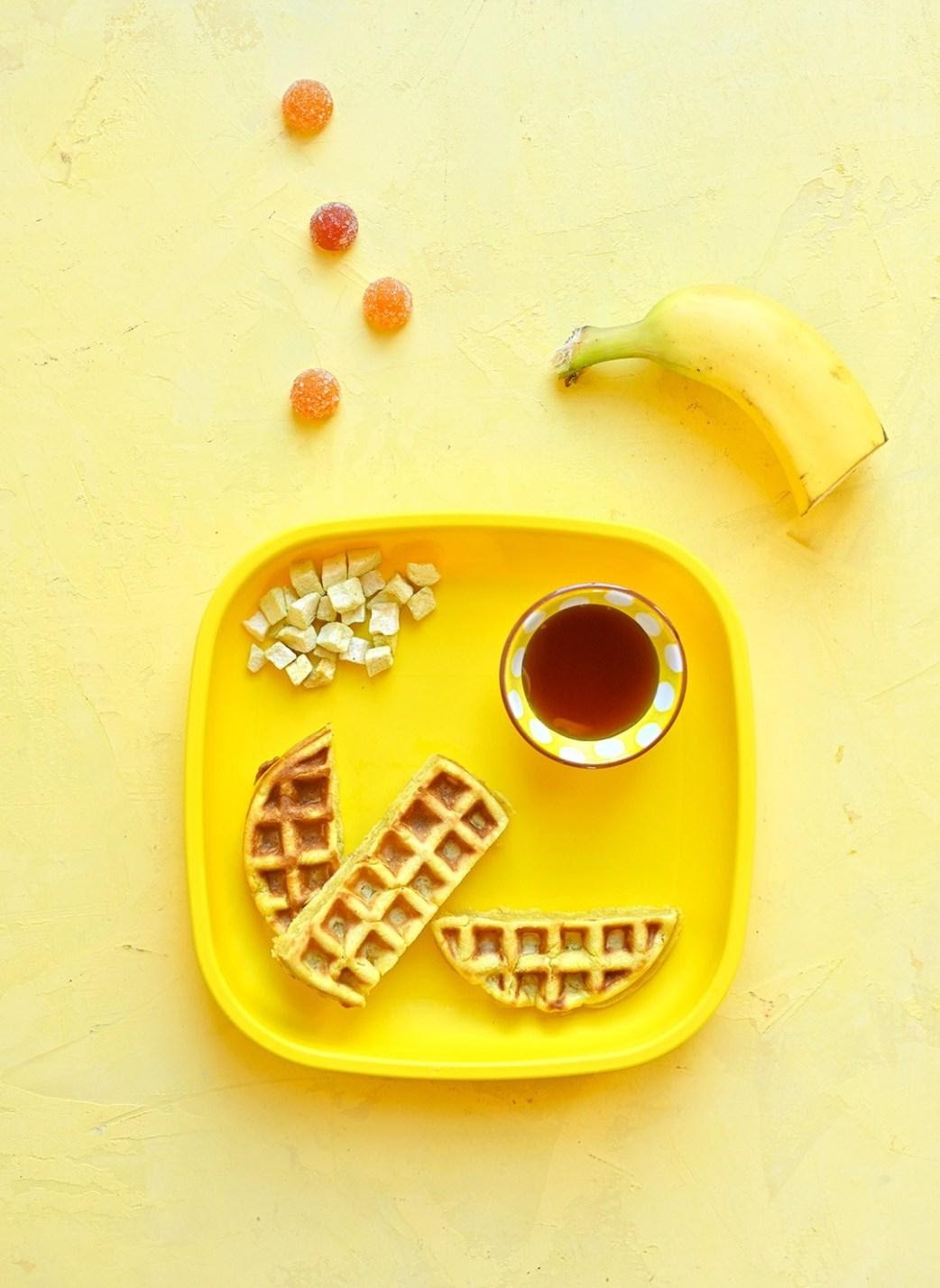 Yellow background with a banana, and yellow kids plate. On the plate is a cut up waffle, small cup with maple syrup, and cut up banana. Next to the plate are SmartyPants gummy vitamins.