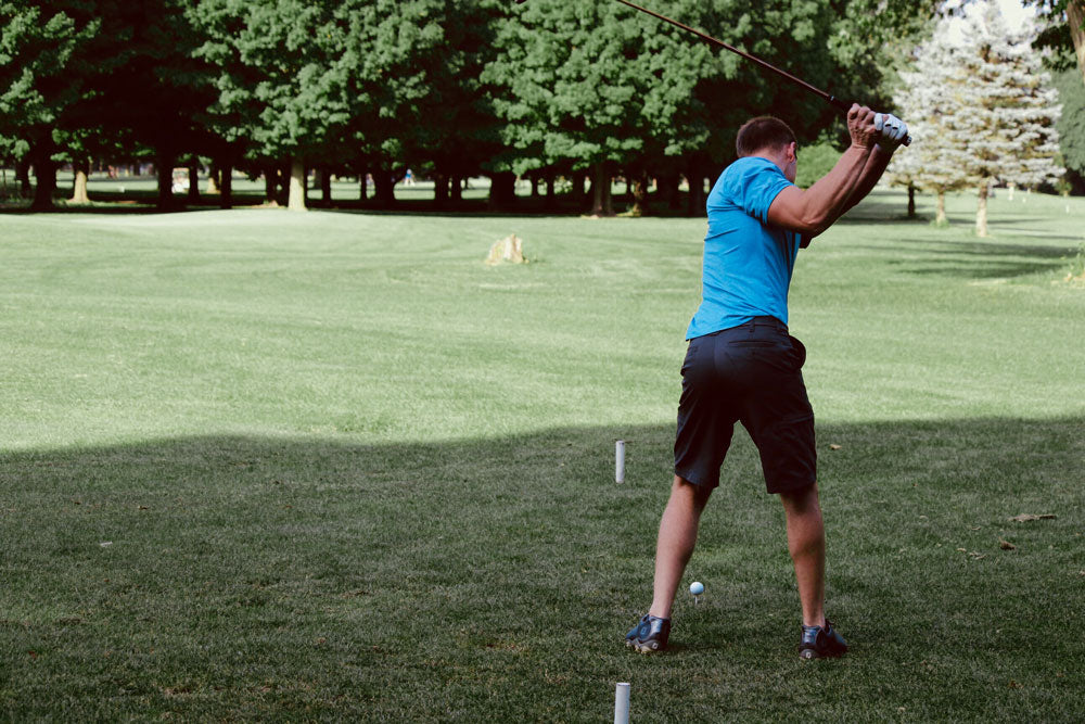 Man playing golf wearing a light blue polo shirt and dark grey shorts.