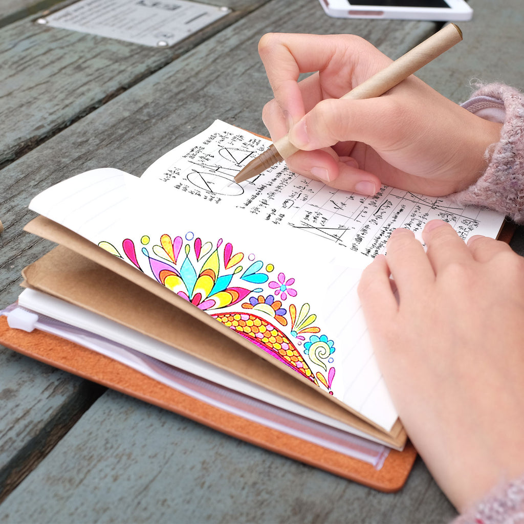 A girl writing on midori style traveler's notebook with ombre pastel galaxy design on a wooden table