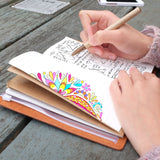 A girl writing on midori style traveler's notebook with boho feathers design on a wooden table
